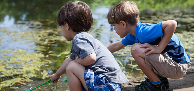 two boys exploring a pond