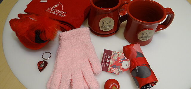 Valentine's Day featured products including pink gloves, a red reusable bag, red mugs, a red cardinal plush toy and a red knit hat.