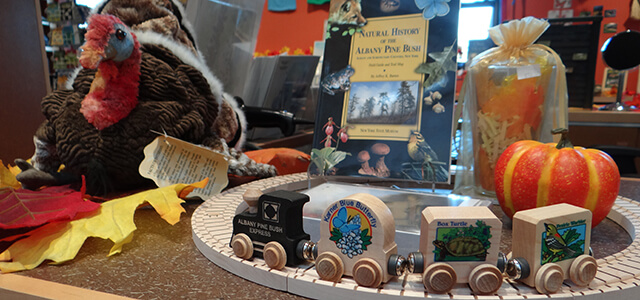 Fall selection of products for sale including a pine bush train set, a turkey puppet and a gift pint glass stuffed with pine bush items