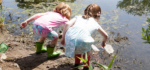 Young children exploring a vernal pond in boots