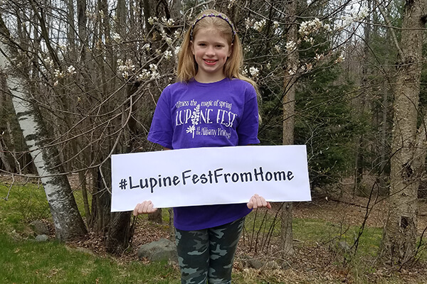 Person with sign that says #Lupine Fest From Home