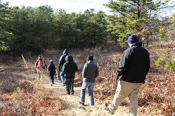 People hiking down trail.