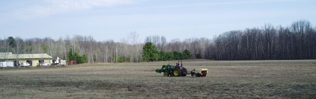 A tractor driving over sand in the preserve planting seeds of native plants.