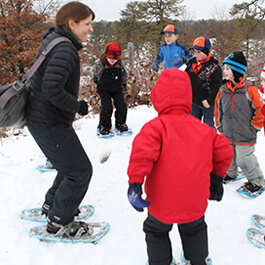 Educator showing students how to snowshoe