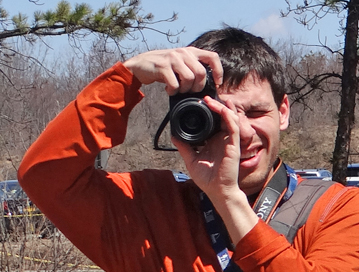A photo of a man in an orange shirt with a camera pointed at the viewer.