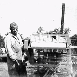 Historic image of a man working on a machine.
