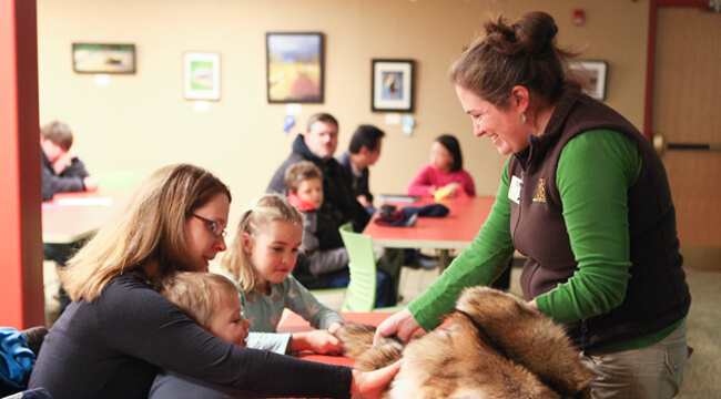 An educator at the Discovery Center holds a coyote pelt for program participants to touch.