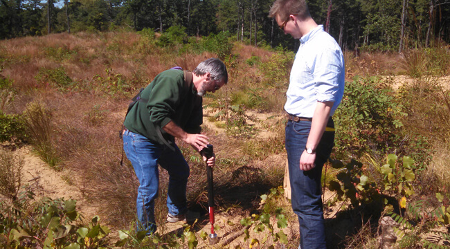 Two researchers collecting a soil sample in the preserve.